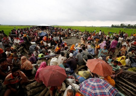 Rohingya refugees sit as they are temporarily held by the Border Guard Bangladesh (BGB) in an open area after crossing the border, in Teknaf